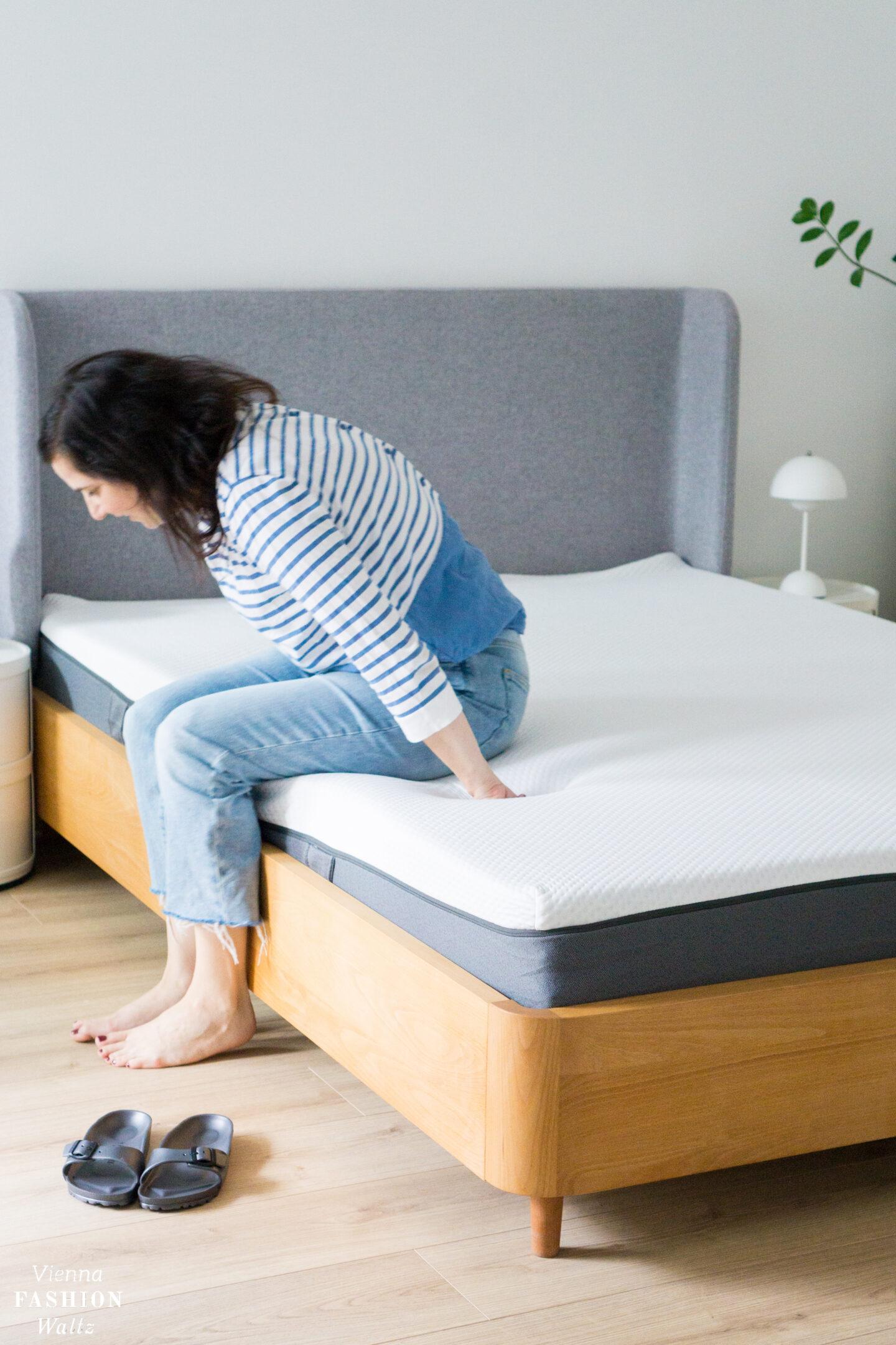Frau sitzt auf Bett